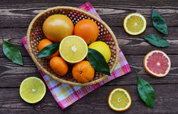 Citrus fruits in a basket lie on a wooden table. Stock Photo