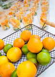 Citrus fruits in basket ready to make juice with glasses in the background. Royalty Free Stock Photo