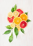 Citrus fruits composing with green leaves on white wooden stock images