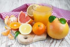 Citrus fruits and fresh orange juice. Variation of Citrus Fruits with leaves  and glass of juice on table Stock Photography