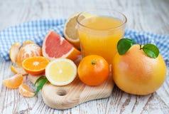 Citrus fruits and fresh orange juice. Variation of Citrus Fruits with leaves  and glass of juice on table Royalty Free Stock Photography