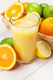 Citrus fruits and glass of juice. Oranges, limes and lemons Stock Photos