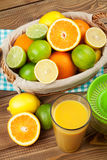 Citrus fruits and glass of juice. Oranges, limes and lemons Royalty Free Stock Photos