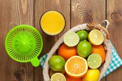 Citrus fruits and glass of juice. Oranges, limes and lemons Royalty Free Stock Images
