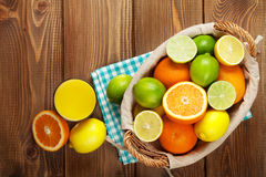 Citrus fruits and glass of juice. Oranges, limes and lemons Stock Image