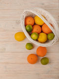 Citrus fruits - lemons, oranges and limes on a light wooden back royalty free stock image