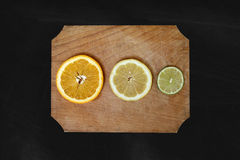 Citrus Fruits. Orange, lime and lemon on dark background Stock Photos