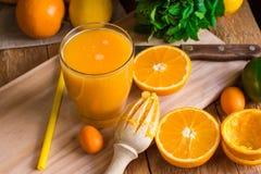 Citrus fruits oranges lemons lime cumquat, fresh mint, reamer, freshly pressed juice in glass on table Stock Images