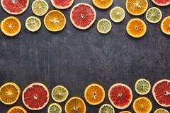 Citrus fruits pattern of lemon, orange and grapefruit on black stone background. stock image