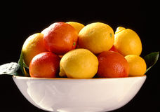 Citrus fruits in plate on black background Royalty Free Stock Photography