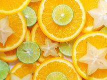 Citrus fruits slices background. Abstract backdrop with slices of lime, orange and carambola stars. Closeup and texture, top view. Citrus fruits slices royalty free stock image