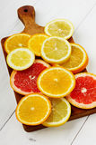 Citrus fruits slices on a brown wooden board. On a white surface Stock Photography