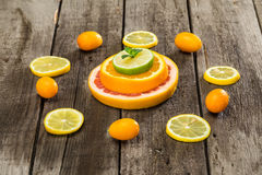 Citrus fruits slices and kumquats on wooden table Royalty Free Stock Photo