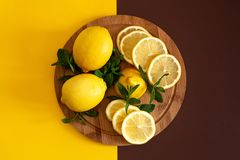 Citrus fruits on a yellow background with copy space. Top view slices of yellow natural lemon on a wooden board - ingredient for stock photo