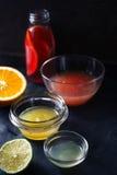 Citrus fruktsaft i den olika glass bunken på den mörka stenbakgrunden arkivbild