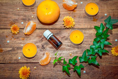 Citrus and herbs aroma oil concept. Essential glass bottle, tangerine, yellow aroma candles , orange daisy flowers  and ivy branch with green leaves on a Stock Images