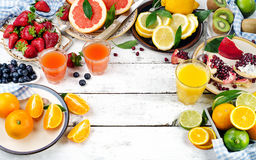 Citrus juice, fresh fruits and berries on a white wooden backgro Royalty Free Stock Photos