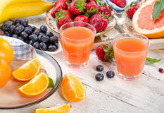 Citrus juice, fruits and berries on wooden background. Healthy e Royalty Free Stock Image