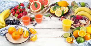 Citrus juice, fruits and berries on a wooden background. Royalty Free Stock Photography