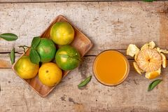Citrus juice in glass and fresh mandarin orange on wooden backgr. Ound Royalty Free Stock Photo