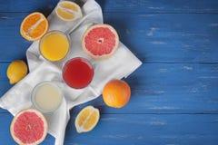 Citrus juice with pieces of fruit on a blue wooden background. Lemon, orange, grapefruit Top view stock photo