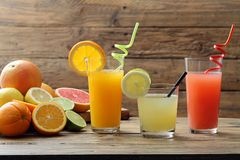 Citrus juice three glasses with orange fruit lemon and grapefruit. Rustic background royalty free stock image