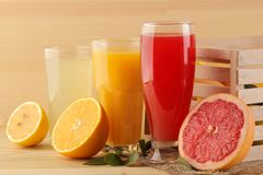 Citrus juices. orange, lemon and grapefruit juice with fresh fruits in a box on a natural wooden background stock images
