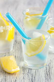 Citrus lemonade with lemon wedges and blue straw.Cold drink with lemon and ice cubes. Royalty Free Stock Images