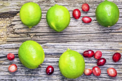 Citrus lime fruits with cranberries on wooden boards Royalty Free Stock Image