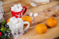 Citrus, marshmallows and Christmas attributes on the surface of a wooden table stock images