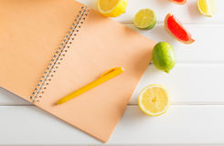 Citrus with notebook on wooden table Stock Images