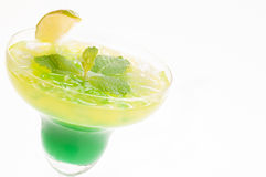 Citrus Paradise Cocktail. Made from Midori melon, white rum, pineapple, lime juice and garnishes with lime wedge and fresh mints leaves Stock Images