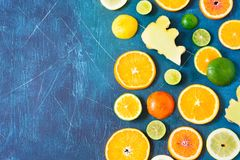 Citrus pattern on blue background with copy space. Assorted citrus fruits. Slices of orange, tangerine, lemon, lime and ginger. To stock images