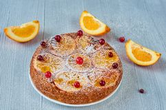 Citrus pie with caramelized oranges and powdered fresh red berries on the gray surface. Just backed pie with raw orange slices. And cranberries on the gray Royalty Free Stock Photography