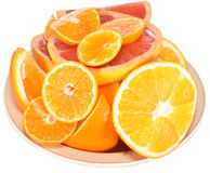 Citrus on a plate. Oranges and grapefruits are cut and lie on a plate Royalty Free Stock Photography