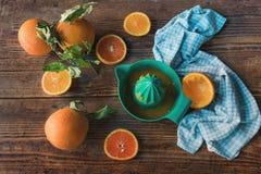 Citrus press med klippt apelsiner och fruktsaft arkivbild