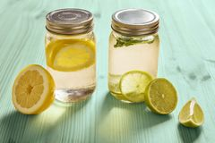 Citrus sodas with fruit pieces on turquoise wood. Two glass jars with lid, one with cold water and slices of lemon and another with slices of lime and mint, are Royalty Free Stock Photo