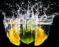 Citrus Splash. Citrus fruit in splash of water. Black background Royalty Free Stock Images