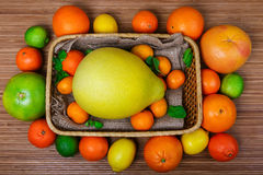 Citrus in a wicker basket on wooden background Stock Image