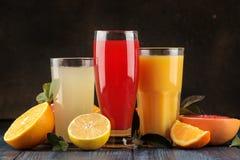 Citrusa fruktsafter Apelsin, grapefrukt och citronjuice med nya frukter på en blå trätabell royaltyfri fotografi