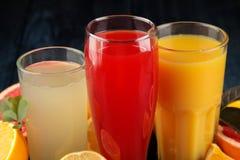 Citrusa fruktsafter Apelsin, grapefrukt och citronjuice med nya frukter på en blå trätabell royaltyfria foton