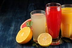 Citrusa fruktsafter Apelsin, grapefrukt och citronjuice med nya frukter på en blå trätabell Utrymme för text royaltyfria foton