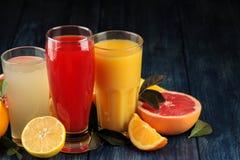 Citrusa fruktsafter Apelsin, grapefrukt och citronjuice med nya frukter på en blå trätabell Utrymme för text royaltyfri fotografi