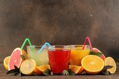 Citrusa fruktsafter Citron, grapefrukt och orange fruktsaft med ny frukt på en brun trätabell Med avstånd för text royaltyfri foto