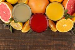 Citrusa fruktsafter Citron, grapefrukt och orange fruktsaft med ny frukt på en brun trätabell Med avstånd för text ovanför sikt arkivbild