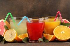 Citrusa fruktsafter Citron, grapefrukt och orange fruktsaft med nya frukter på en brun trätabell fotografering för bildbyråer