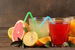 Citrusa fruktsafter Citron, grapefrukt och orange fruktsaft med nya frukter på en brun trätabell arkivbilder