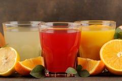 Citrusa fruktsafter Citron, grapefrukt och orange fruktsaft med nya frukter på en brun trätabell royaltyfri bild