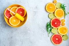 Citrusa skivor med fruktisglassar på åtlöje för bästa sikt för tabellbakgrund upp Royaltyfri Foto