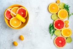 Citrusa skivor med fruktisglassar på åtlöje för bästa sikt för tabellbakgrund upp Royaltyfria Bilder